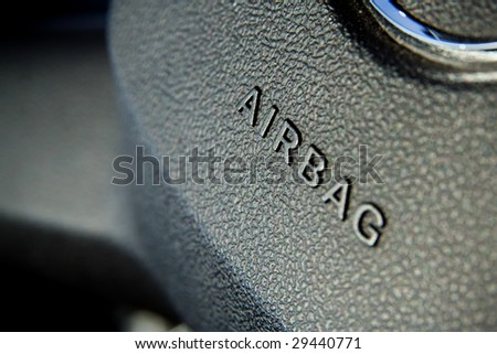 Airbag symbol on steering wheel closeup - stock photo