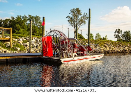 Airboat leaving on guided tour through Louisiana swamps searching for alligators - stock photo