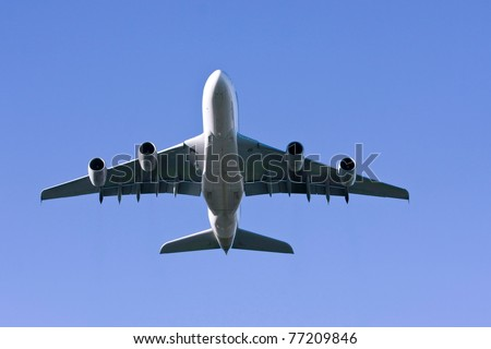 Airbus A380 airliner flying low overhead.