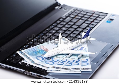 Aircraft and banknotes above laptop
