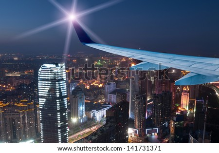 Aircraft at night, over the riverside city. - stock photo