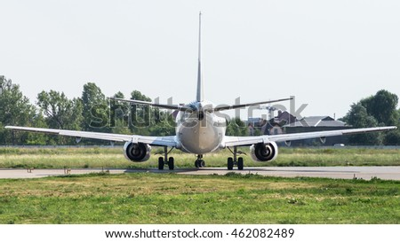 Aircraft back view. Back lit view of a taxiing commercial airplane, ready for departure. White colored jet aircraft with two turbine engines. Aviation copy space and background.