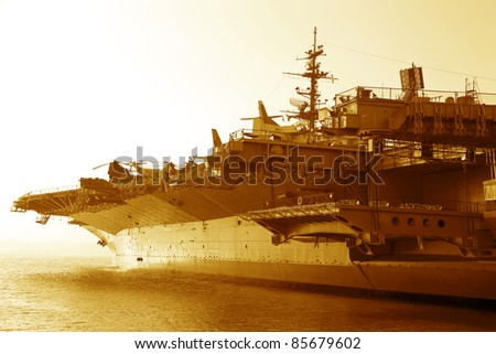 Aircraft carrier in the ocean at sunset - stock photo