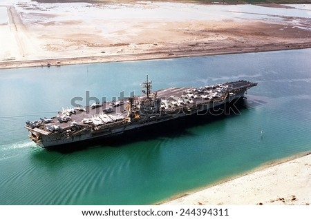 Aircraft carrier JOHN F. KENNEDY in the Suez Canal traveling home to Norfolk Virginia after a seven month deployment during the First Iraq War. 1991. Mar. 1 1991. - stock photo