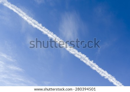 Aircraft Condensation Trails or Contrails of the Plane in the Blue Sky - stock photo