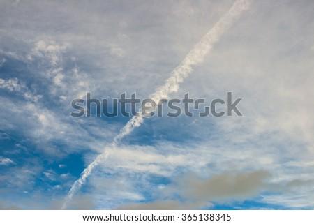 aircraft contrail across cloudy blue sky - stock photo
