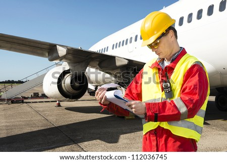 Aircraft engineer with a checklist of several pages on a clipboard - stock photo