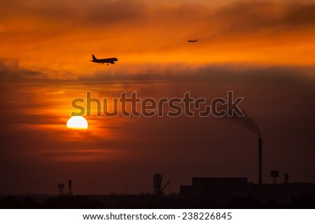 Aircraft. Evening sky and smoke from factories. - stock photo