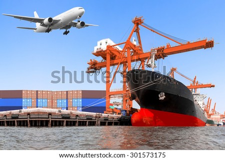 Aircraft flight at airport link with commercial delivery cargo container and container ship being unloaded in the harbor - stock photo