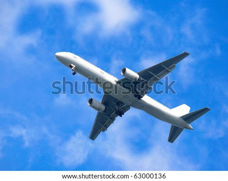 Aircraft flying in blue cloudy sky - stock photo