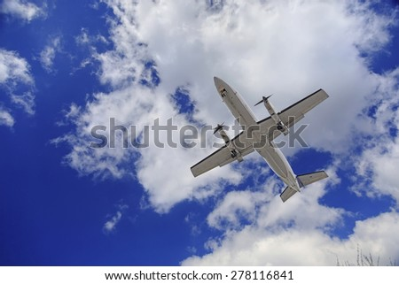 Aircraft flying in blue cloudy sky, closeup view - stock photo