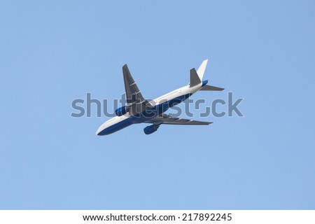 Aircraft flying in blue sky - stock photo