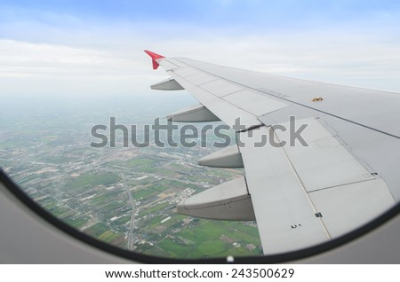 aircraft flying over green field, hanoi city, vietnam - stock photo