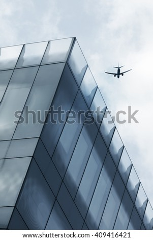 Aircraft flying over office tower