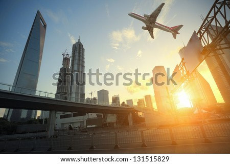Aircraft flying over the modern city buildings over - stock photo