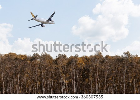 Aircraft flying over tree with blue sky. - stock photo