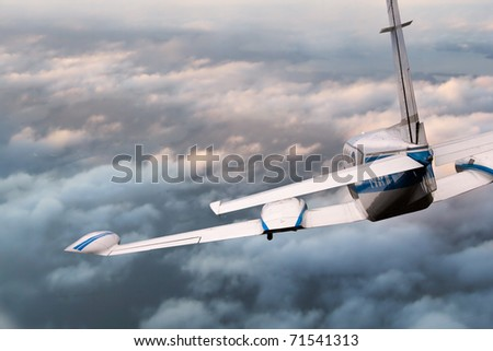Aircraft in flight descending from above  the clouds - stock photo
