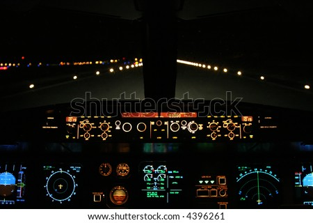 aircraft landing at night with runway ahead - stock photo