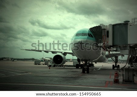Aircraft loading and unloading luggage - stock photo