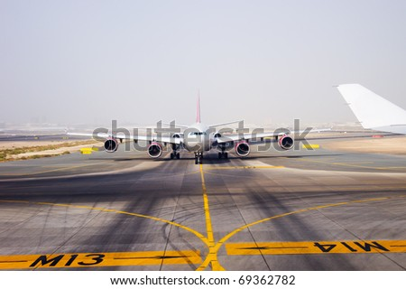 aircraft on landing strip in airport of Dubai - stock photo