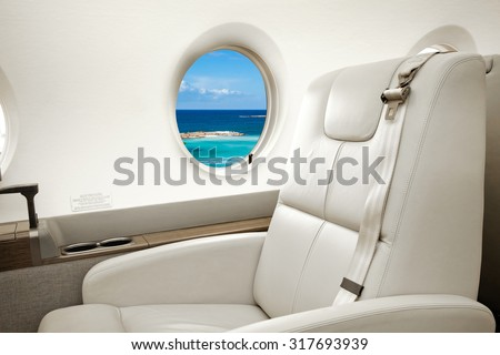 Aircraft porthole with view of sea and beach resort, flight by business class - stock photo