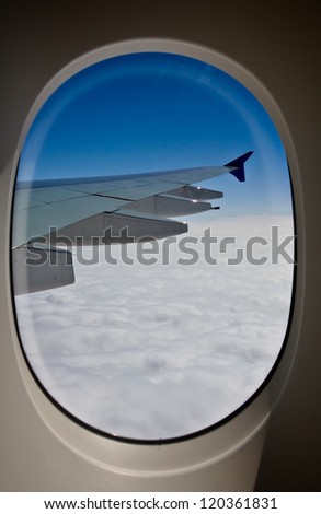 aircraft's wing with blue sky from window - stock photo