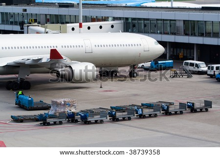 Aircraft standing at gate and being loaded with luggage - stock photo