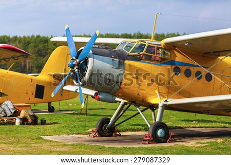 Aircraft standing on green grass in a clear sunny day. Two old yellow airplane in a retro style. - stock photo