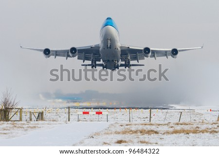 Aircraft taking off in snowy conditions - stock photo