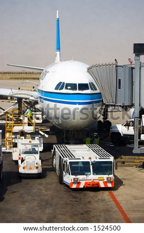 Aircraft tow tractor standing by for push back. - stock photo