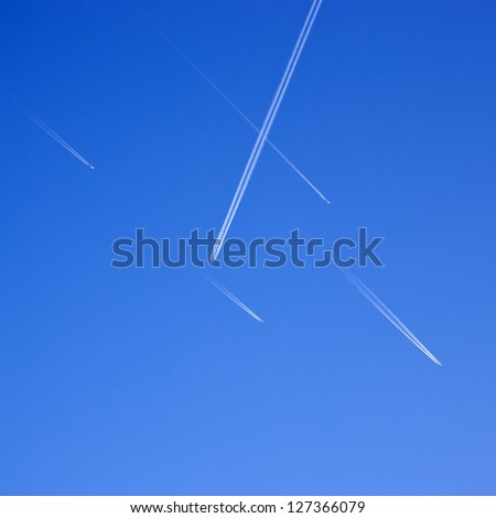 Aircraft traffic. Airliners criss-crossing the blue sky. - stock photo
