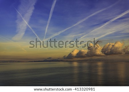 Aircraft trails in cloudy sky over calm sea, at sunset, amazing view - stock photo