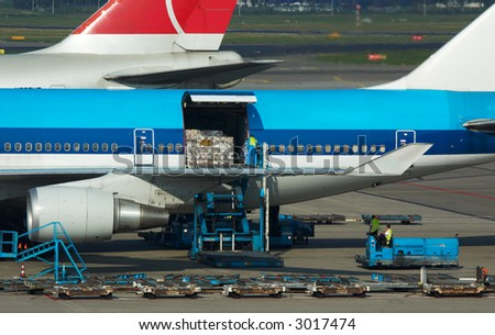 aircraft unloading cargo on airport - stock photo