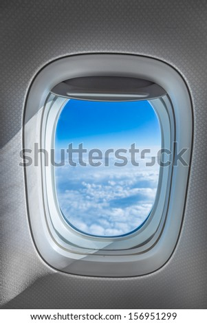 Aircraft Window with plane cruising against bright blue sky and clouds - stock photo
