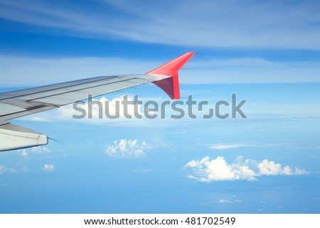 Aircraft wing against bluesky from its windows