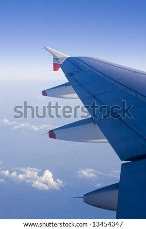Aircraft wing flying high above the clouds - stock photo