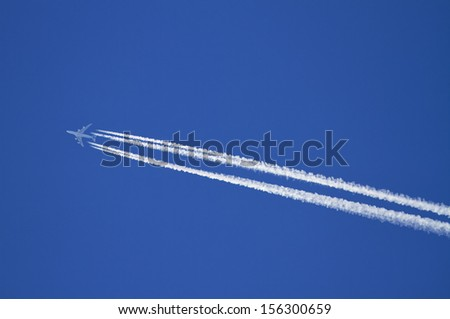 Aircraft with condensation trails on blue sky.