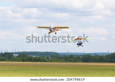 "Airfield Frolovo,Russia - June 29,2014.Festival ""Wings of Parma 2014"".plane and paraglider fly up"
