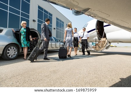 Airhostess and pilot greeting business people before boarding private jet - stock photo