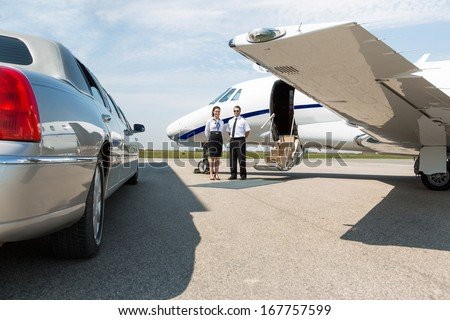 Airhostess and pilot standing neat limousine and private jet at airport terminal - stock photo