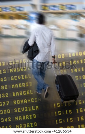 Airline Passenger at the Airport pulling his suitcase - stock photo