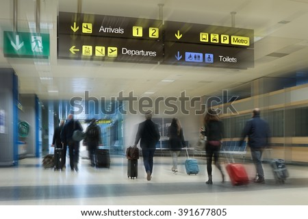 Airline passengers walking inside an Airport with their Luggage