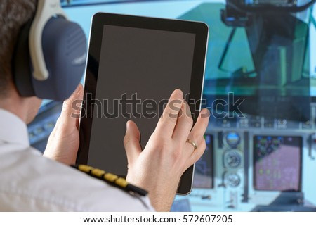 Airline pilot wearing uniform with epauletes using tablet in airplane cockpit