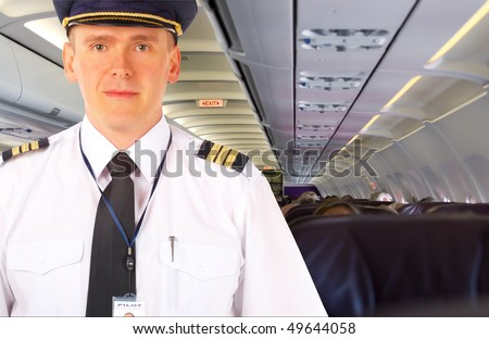 Airline pilot wearing uniform with epaulettes and hat, on board passenger aircraft.