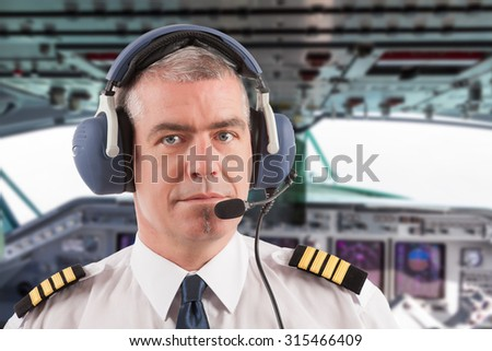 Airline pilot wearing uniform with epaulettes and headset, on board passenger aircraft.  - stock photo