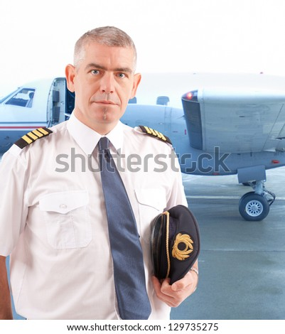 Airline pilot wearing uniform with epaulettes with passenger aircraft in background - stock photo