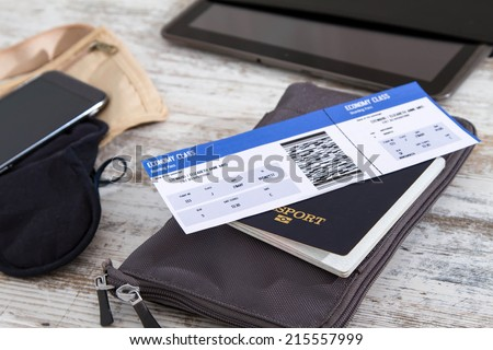 Airline ticket, passport and electronics, preparing to travel  - stock photo