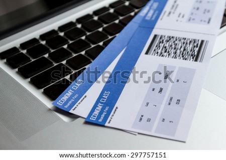 Airline tickets over the keyboard of a laptop - stock photo