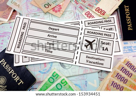 Airline tickets with foreign money and passports - stock photo
