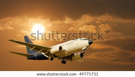 Airliner against glowing sky - stock photo
